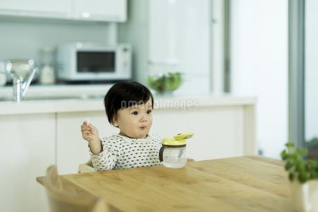 テーブルに座りお菓子を食べる赤ちゃんの写真素材 [FYI01622008]