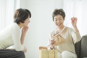娘から貰ったプレゼントを開ける母親の写真素材 [FYI01622021]