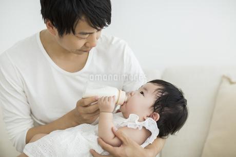 赤ちゃんにミルクを飲ませる父親の写真素材 [FYI01622035]