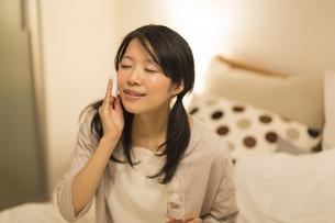 ベッドの上でスキンケアをする女性の写真素材 [FYI01622037]