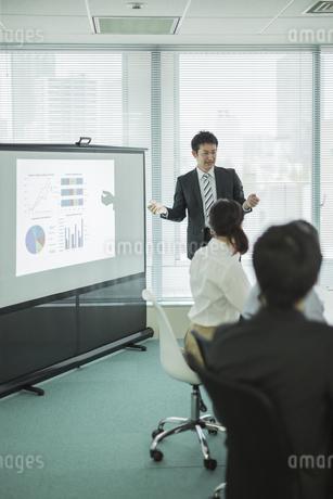 プロジェクターを使用した会議で説明をするビジネスマンの写真素材 [FYI01622045]