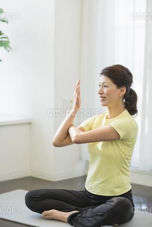 室内でストレッチをする笑顔の中高年女性の写真素材 [FYI01622047]