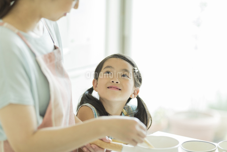キッチンで料理をする母親に寄り添う女の子の写真素材 [FYI01622052]