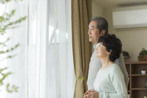 窓辺に立ち外を眺めるシニア夫婦の写真素材 [FYI01622057]