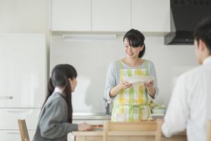 朝食中の家族と会話をする母親の写真素材 [FYI01622090]