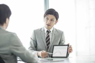 タブレットPCを使用して打ち合わせをするビジネスマンの写真素材 [FYI01622092]