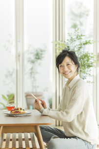 携帯電話を持って笑顔の女性の写真素材 [FYI01622093]