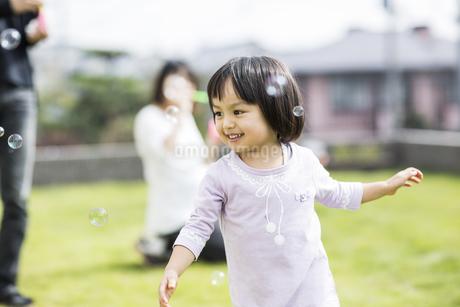シャボン玉を追いかける女の子の写真素材 [FYI01622101]