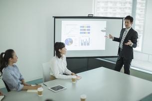 プロジェクターを使用した会議で説明をするビジネスマンの写真素材 [FYI01622118]