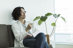 ソファーに座ってコーヒーを飲む男性の写真素材 [FYI01622120]