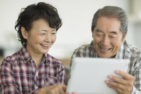 タブレットPCを見るシニア夫婦の写真素材 [FYI01622122]