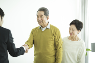 握手をするシニア夫婦とビジネスマンの写真素材 [FYI01622130]