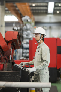 機械を操作する作業服の男性の写真素材 [FYI01622131]