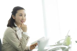 オフィスデスクで手帳を持つビジネスウーマンの写真素材 [FYI01622132]