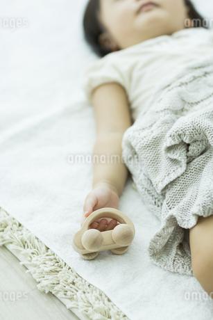 眠りながら木の玩具を持つ赤ちゃんの手元の写真素材 [FYI01622159]