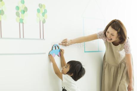 壁のイラストの前で遊ぶ親子の写真素材 [FYI01622160]
