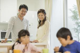キッチンから子供たちを見守る夫婦の写真素材 [FYI01622161]