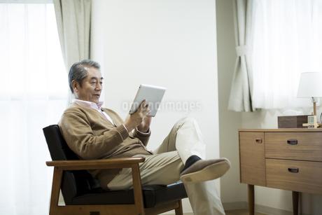 タブレットPCを操作するシニア男性の写真素材 [FYI01622168]