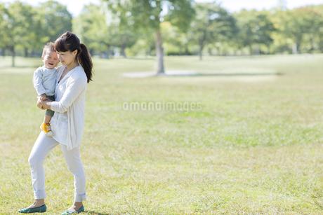 赤ちゃんを抱っこし歩く母親の写真素材 [FYI01622175]