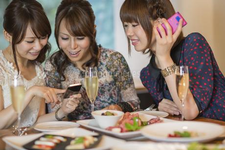 女子会でスマートフォンを見せて微笑む若い女性の写真素材 [FYI01622181]