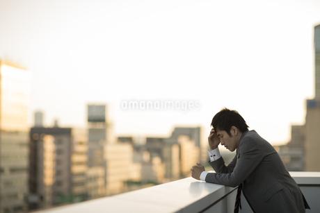 屋上で落ち込むビジネスマンの写真素材 [FYI01622182]