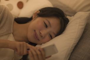 ベットに寝転んでスマートフォンを操作する女性の写真素材 [FYI01622184]