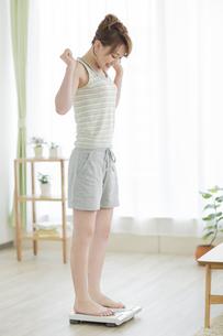 体重計に乗って喜ぶ女性の写真素材 [FYI01622194]