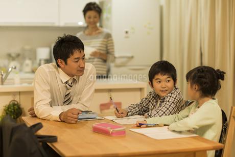 子供たちの勉強を見る父親の写真素材 [FYI01622199]