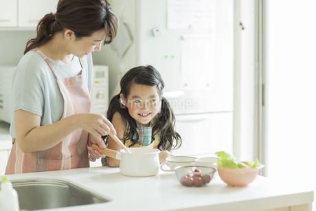 キッチンで料理をする母親に寄り添う女の子の写真素材 [FYI01622214]
