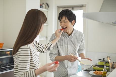 若い男性にトマトを食べさせる若い女性の写真素材 [FYI01622216]