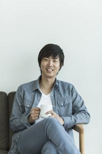 ソファーに座って笑顔の男性の写真素材 [FYI01622225]