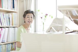 ピアノを弾く中高年女性の写真素材 [FYI01622243]