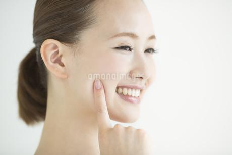 頬に指をあてる女性のスキンケアイメージの写真素材 [FYI01622247]
