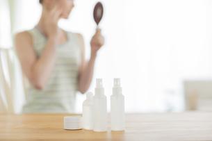 テーブルに置かれた化粧品と手鏡を見る女性の写真素材 [FYI01622267]