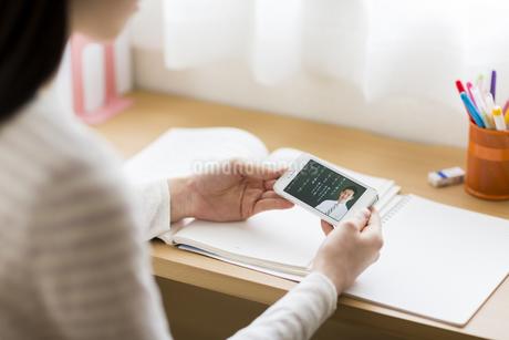 スマートフォンを見て勉強をする女子学生の手元の写真素材 [FYI01622268]