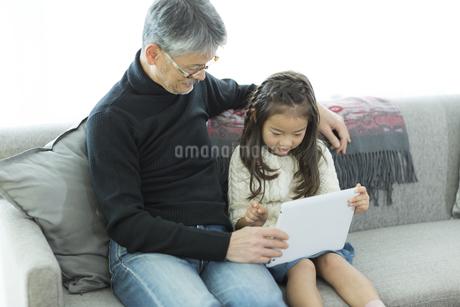 タブレットPCを見る祖父と孫の写真素材 [FYI01622287]