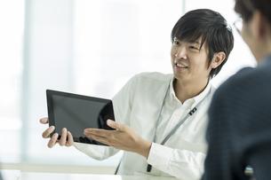 タブレットPCを使用し打ち合わせをするビジネスマンの写真素材 [FYI01622289]