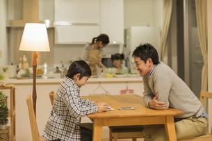 テーブルでタブレットPCを見る親子の写真素材 [FYI01622292]