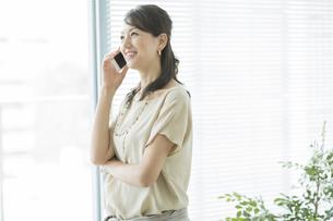 スマートフォンで話すビジネスウーマンの写真素材 [FYI01622306]