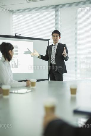 プロジェクターを使用した会議で説明をするビジネスマンの写真素材 [FYI01622311]