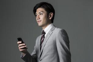スマートフォンを持つビジネスマンの写真素材 [FYI01622314]