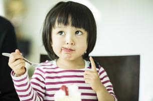 頬っぺたについたクリームを舐める女の子の写真素材 [FYI01622316]