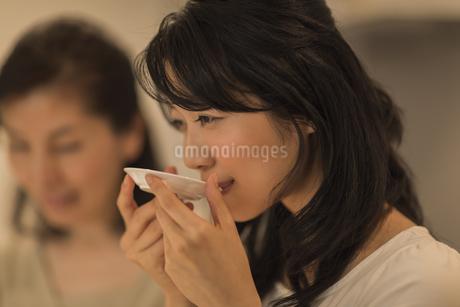 キッチンで味見をする娘の写真素材 [FYI01622318]
