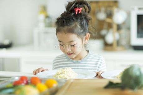 料理をみて微笑む女の子の写真素材 [FYI01622324]