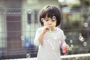 シャボン玉で遊ぶ女の子の写真素材 [FYI01622326]
