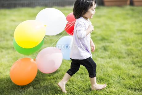 風船を持って走る女の子の写真素材 [FYI01622330]