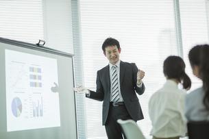 プロジェクターを使用した会議で説明をするビジネスマンの写真素材 [FYI01622346]