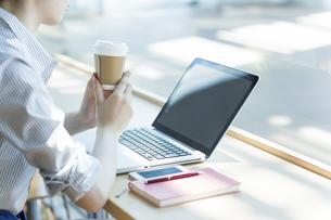 カフェでパソコンをするビジネスウーマンの手元の写真素材 [FYI01622369]