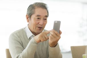 スマートフォンを操作するシニア男性の写真素材 [FYI01622377]