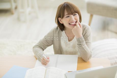 部屋で勉強をする若い女性の写真素材 [FYI01622381]